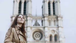 Beautiful teenager female taking photos of Notre Dame on retro film camera in Paris, France, famous cathedral.