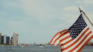 Beautiful view from the boar on Manhattan in New York, USA. American flag waving on the wind, East river.
