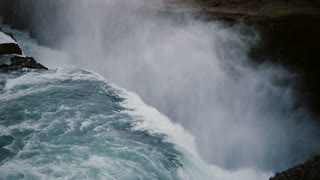 Beautiful view of the Gullfoss waterfall in Iceland. Turbulent flow of water falls down with splashes and foam.