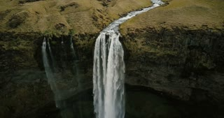 Beautiful view of valley with powerful river flows and falls down. Aerial view of Seljalandsfoss waterfall in Iceland.
