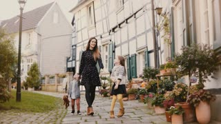 Beautiful woman walking with two children. Holding hands. European mother, girl and boy together. Hattingen, Germany 4K.