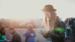 Beautiful young European woman in stylish hat using smartphone app in blurry busy crowded sunset street slow motion.