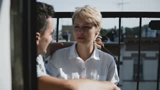 Beautiful young European woman talking to man. Couple sitting at a small sunny apartment balcony talking to each other.