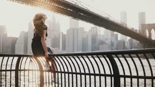 Beautiful young girl in sunglasses sitting on river embankment fence near Brooklyn Bridge, New York, enjoying view 4K.