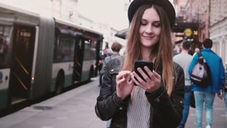 Beautiful young happy European girl in stylish hat walking along busy city street using smartphone app slow motion.