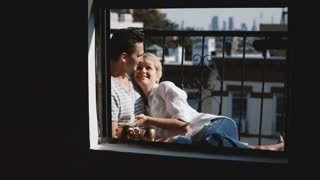 Beautiful young man and woman sitting close together, hugging and chatting at a lovely small sunny apartment balcony.