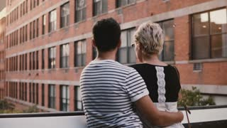 Beautiful young man and woman standing and hugging on a bridge talking, enjoying amazing urban scenery and buildings.