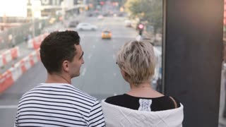 Beautiful young multiethnic romantic couple standing on a bridge enjoying lovely New York street view and kissing gently