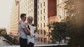 Beautiful young romantic couple standing and hugging on an amazing New York sunset bridge, urban buildings background.