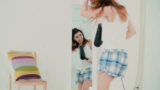Beautiful young woman feeling happy and singing while using hairdryer, wind blowing the hair. Slow motion.