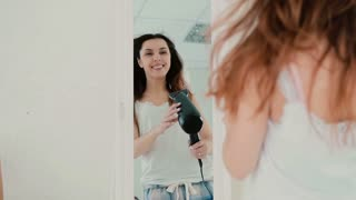 Beautiful young woman feeling happy and singing while using hairdryer. Wind inflates hair. Slow motion.