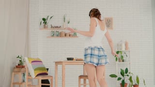 Beautiful young woman feeling happy, jumping and dancing. Brunette girl in pajamas having fun in morning at home.