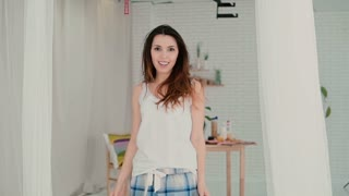 Beautiful young woman feeling happy, jumping and dancing. Brunette girl in pajamas having fun in morning. Slow motion.