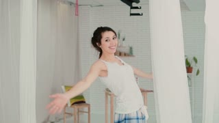 Beautiful young woman feeling happy, playing with hair. Brunette girl in pajamas spinning. Slow motion.
