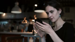 Beautiful young woman sitting in cafe and using the smartphone. Attractive female typing message on touchscreen.