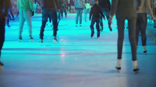 Big crowd of young people skating on the indoor ice rink with manufactured ice on it and colored light.