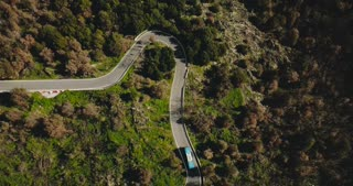 Blue bus turns left on a mountain road aerial view. Dangerous narrow forest driveway. Traffic road safety. Travel 4K.