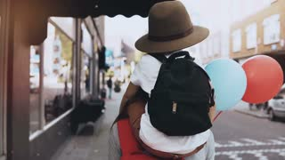 Boy child on mom's shoulders, two air balloons. Mother and son in hat with backpack walk together along the street. 4K.