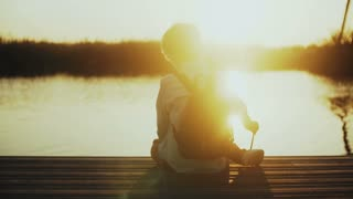 Boy plays with stick on a lake pier. Back view. Little child with backpack sits on a quay. Amazing sun lens flare. 4K.