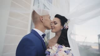 Bride and groom under a wedding veil. Loving couple have a tenderly time together. Man and woman kiss in wedding day.