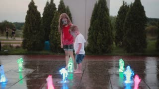 Brother and sister playing at the colored fountain together. Boy and girl touching water jet, having fun.