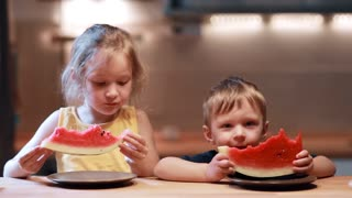 Brother and sister sitting at the table on kitchen. Boy and girl eating juicy watermelon, looking to the camera.
