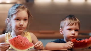 Brother and sister sitting at the table on kitchen. Boy and girl eating juicy watermelon on the plate, bites the pieces.