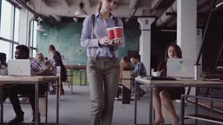 Brunette female manager comes to modern office. Young woman greets with colleagues, brings coffee to friend. slow mo