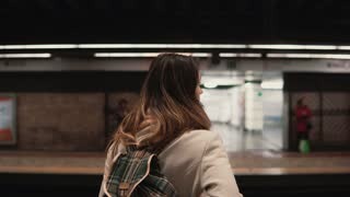 Brunette woman standing on railway station and waiting for her train. Girl in underground at evening looks on fast trams