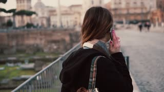 Brunette woman talking on a phone during walking on a Roman Forum. Girl tells about the journey in Rome, Italy.