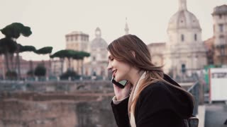 Brunette woman walking in city centre, Roman Forum. Female tourist talking on the phone and smiling.
