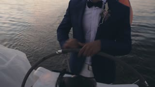 Businessman in suit standing behind a steering wheel on the sailboat. Young sailor driving the yacht on sunset.