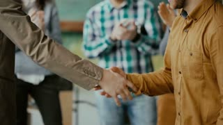 Businessman shakes hand to new male employee, taps on the shoulder. Group of people clapping on a background.