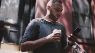Busy handsome European man walking down the stairs of a Brooklyn house with smartphone and coffee slow motion close-up.