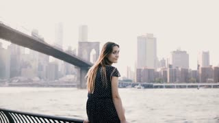 Camera closing up on beautiful European girl looking back and smiling, sitting near New York Brooklyn Bridge panorama.