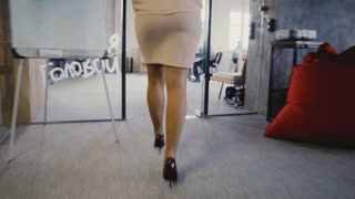 Camera follows attractive female team leader enter office, come up to multiethnic workers, talk and sign documents 4K.