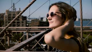 Camera follows beautiful happy European brunette businesswoman in stylish sunglasses walking along Brooklyn Bridge 4K.