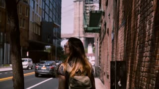 Camera follows Caucasian female tourist in fashionable sunglasses exploring old streets of New York City, slow motion.