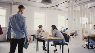 Camera follows Caucasian manager coming up and talking to colleagues. Happy multiethnic employees in modern office 4K.