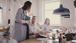 Camera follows female CEO motivating workers. Woman boss chats with colleagues, gives them directions in loft office 4K.