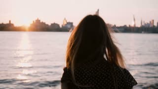 Camera follows girl with hair blowing in the wind run towards water edge, stop and look at New York sunset skyline 4K