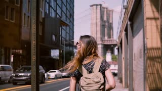 Camera follows happy Caucasian girl in fashionable sunglasses with hair blowing in the wind in New York City slow motion