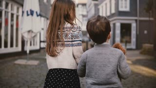 Camera follows little girl and boy walking together. Back view. Two kids wander around old town. Brother and sister. 4K.