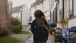 Camera follows little girl running on paved road. Back view. Ancient half-timbered houses in Hattingen, Germany. 4K.