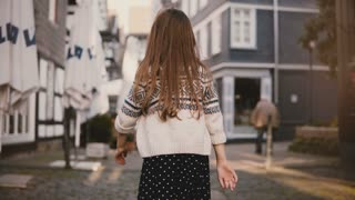 Camera follows little girl walking in old town. Back view. Female kid, long hair, wandering around ancient streets. 4K.