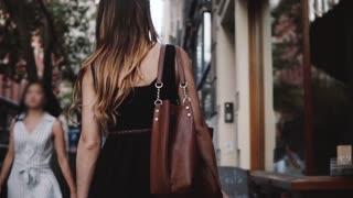 Camera follows of young female fashion blogger with stylish bag walking along beautiful small city street slow motion.