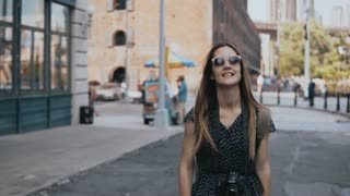 Camera follows playful excited European tourist girl with backpack in sunglasses, raising hands and smiling happy 4K.
