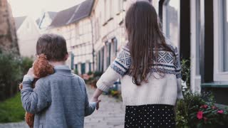 Camera follows two little kids walk holding hands. Slow motion back view. Girl and boy wander around old town. Siblings.
