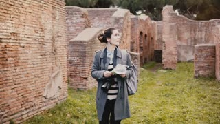 Camera follows young excited traveler woman with backpack expolring ancient historic red brick ruins of Ostia, Italy.