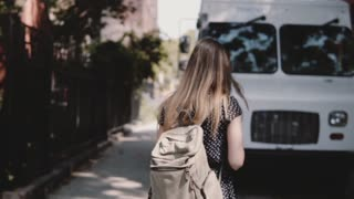 Camera follows young female tourist with backpack crossing the street near white van, enjoying leisure walk slow motion.